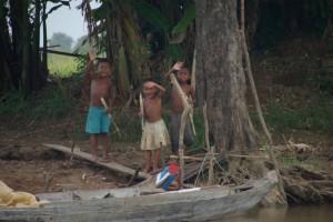Kinder der Familien, die in den Doerfern entlang des Flusses leben - alle lachen und winken