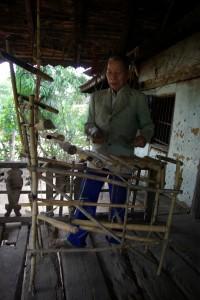 Der Dorfaelteste eines Bahnar-Minderheitendorfs zeigt uns sein selbstgebautes Musikinstument (aehnlich einem Xylophon)