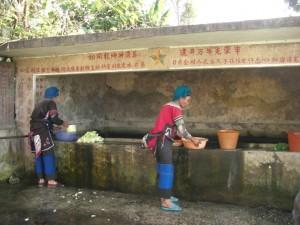 ...beim Dorfbrunnen auf Gemuese waschende Frauen in ihrer traditionellen Tracht...