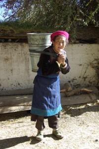 Die Grossmutter beim Wassertragen... gute 30kg am Ruecken...