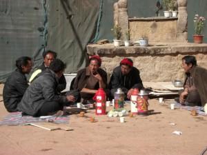 Pilger beim Buttertee vor dem Tempel - der Tee wird praktischerweise immer in Thermosflaschen mitgebracht
