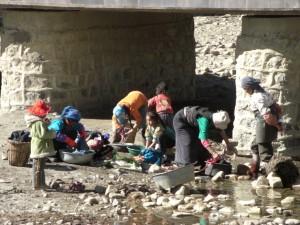am Weg zum Kloster tibetisches Leben - Waeschewaschen im Fluss, der durch den Ort fliesst