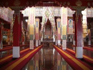 im Inneren die Versammlungshalle mit den Meditationskissen am Boden