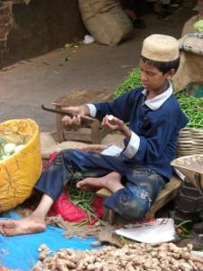 man sieht viele arbeitende Menschen wie dieser Junge hier beim Ingwerschneiden