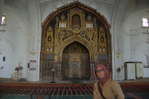 Dani, brav mit Kopftuch vor dem Mihrab, der Gebetsnische, dem Allerheiligsten der Moschee